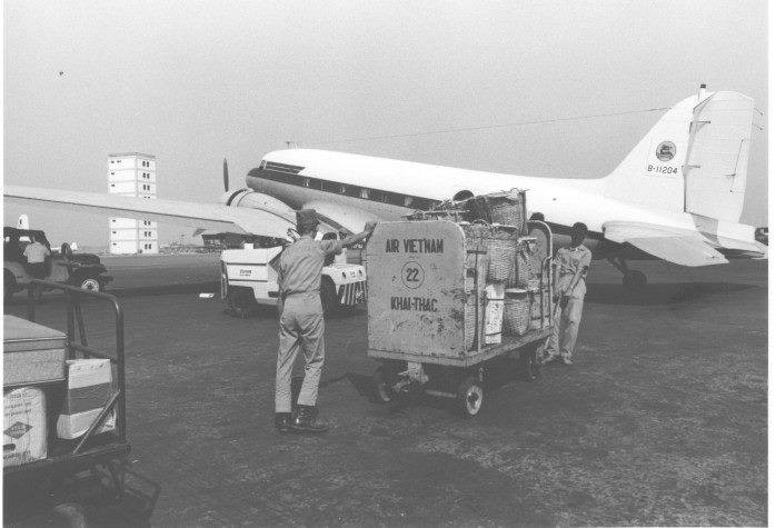 Air Vietnam cargo handlers load a DC-3 with goods bound for a rural town. The new Tan Son Nhut control tower under construction (left, background) is due for completion by June 1970.