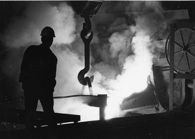 Silhouetted By Smoke And Steam - A VICASA worker guides a giant bucket as it dips molten steel from a pit beneath one of the mill's furnaces.