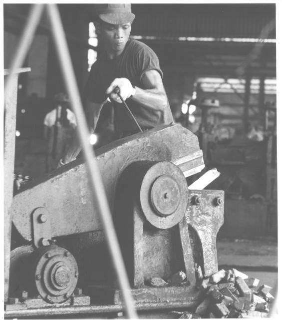 His muscles straining, a Vietnamese worker at the Bien Hoa steel plant uses a hydraulic clipper to remove inferior steel from the end of each ingot.