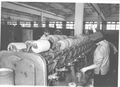 Women workers at the Vinatefinco plant in Gia Dinh operate drawing equipment used to test jute and kenaf yarn. Because of the war's drain on manpower, women make up a large part of the textile industry's work force