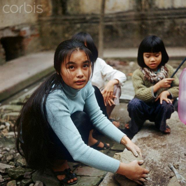 """01 Mar 1973, Hanoi, Vietnam --- Vietnamese girls in a back yard, photographed in March 1973 in North Vietnam. Only a few weeks before, the peace agreement was signed on the 27th of January in 1973 in Paris and the war against North Vietnam ended. The United States of America flew about 2,000 air attacks on cities and targets in North Vietnam during the """"Christmas bombings"""" in 1972. Photo: Werner Schulze --- Image by © Werner Schulze/dpa/Corbis © Corbis. All Rights Reserved."""