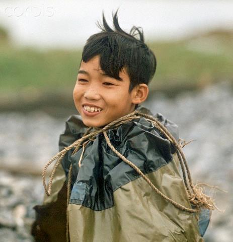 """01 Mar 1973, Hanoi, Vietnam --- A Vietnamese boy with a rain coat, photographed in March 1973 in North Vietnam. Only a few weeks before, the peace agreement was signed on the 27th of January in 1973 in Paris and the war against North Vietnam ended. The United States of America flew about 2,000 air attacks on cities and targets in North Vietnam during the """"Christmas bombings"""" in 1972. Photo: Werner Schulze --- Image by © Werner Schulze/dpa/Corbis © Corbis. All Rights Reserved."""