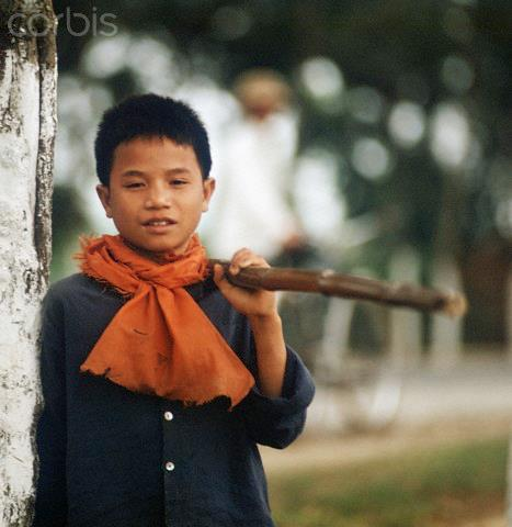 01 Mar 1973, Hanoi, Vietnam --- A Vietnamese boy with a wooden bar and a red scarf around the neck, photographed in March 1973 in North Vietnam. Only a few weeks before, the peace agreement was signed on the 27th of January in 1973 in Paris and the war against North Vietnam ended. The United States of America flew about 2,000 air attacks on cities and targets in North Vietnam during the