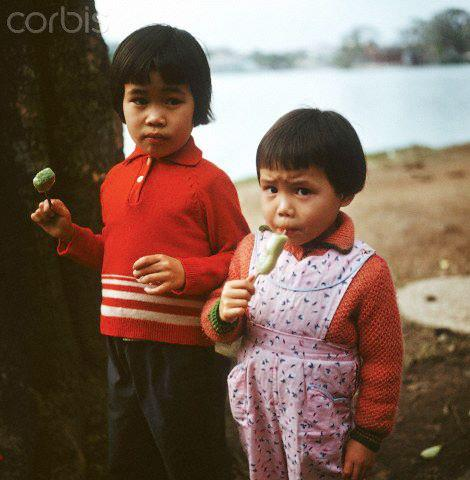 """01 Mar 1973, Hanoi, Vietnam --- Two Vietnamese children eat sweets, photographed in March 1973 in North Vietnam. Only a few weeks before, the peace agreement was signed on the 27th of January in 1973 in Paris and the war against North Vietnam ended. The United States of America flew about 2,000 air attacks on cities and targets in North Vietnam during the """"Christmas bombings"""" in 1972. Photo: Werner Schulze --- Image by © Werner Schulze/dpa/Corbis © Corbis. All Rights Reserved."""