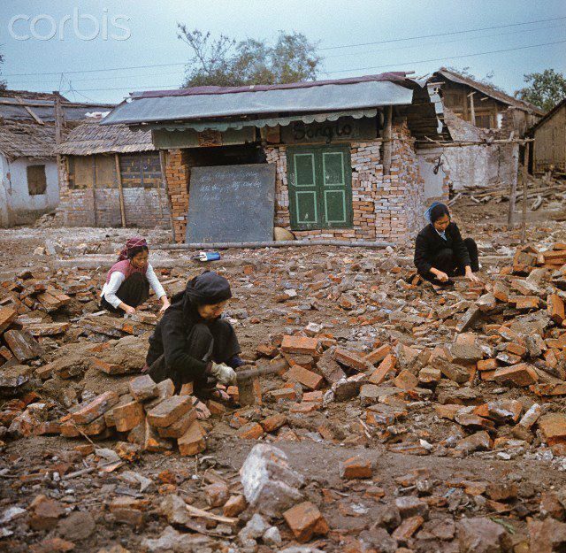 """01 Mar 1973, Hanoi, Vietnam --- Vietnamese women clean bricks for the reconstruction on a field of debris between war-destroyed houses in Kham Thien, a part of Hanoi in North Vietnam in March 1973. The United States of America flew about 2,000 air attacks on cities and targets in North Vietnam during the """"Christmas bombings"""" in 1972. The peace agreement was signed on the 27th of January in 1973 in Paris. Photo: Werner Schulze --- Image by © Werner Schulze/dpa/Corbis © Corbis. All Rights Reserved."""
