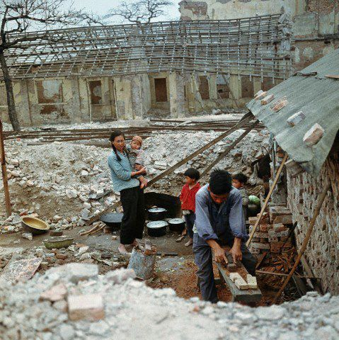 "01 Mar 1973, Haiphong, Vietnam --- A Vietnamese family in the middle of war-destroyed buildings in the harbour city Haiphong in North Vietnam, photographed in March 1973. The United States of America flew about 2,000 air attacks on cities and targets in North Vietnam during the ""Christmas bombings"" in 1972. The peace agreement was signed on the 27th of January in 1973 in Paris. Photo: Werner Schulze --- Image by © Werner Schulze/dpa/Corbis © Corbis. All Rights Reserved."