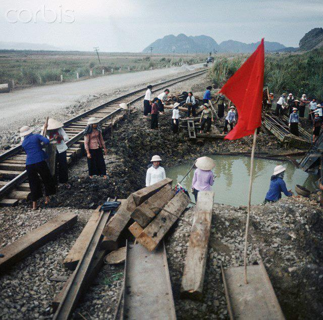 01 Mar 1973, Hanoi, Vietnam --- A red flag blows at a construction site around a bomb crater at a railway line along Street Number 1, where young Vietnamese women of a so-called