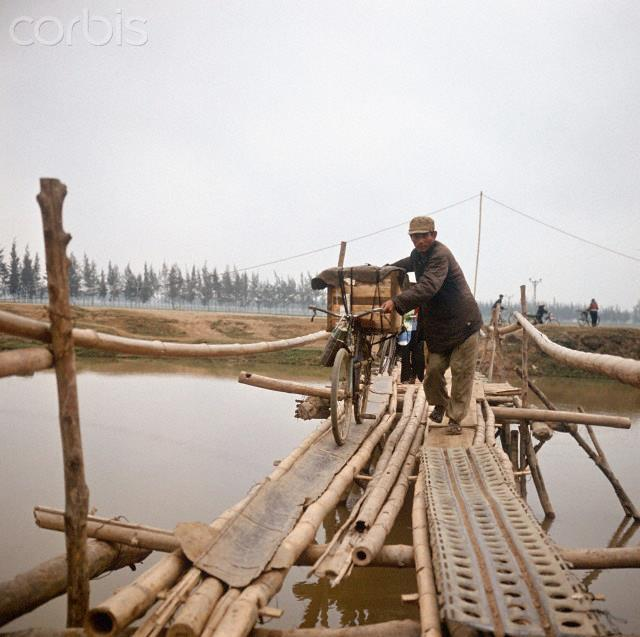 """01 Mar 1973, Dong Hoi, Vietnam --- A Vietnamese with a bicycle loaded with luggage, crosses a provisional bridge made out of bamboo and other material, photographed in March 1973 in North Vietnam, south-eastern of Dong Hoi near the 17th degree of latitude, which is regarded as the border to South Vietnam. The United States of America flew about 2,000 air attacks on cities and targets in North Vietnam during the """"Christmas bombings"""" in 1972. The peace agreement was signed on the 27th of January in 1973 in Paris. Photo: Werner Schulze --- Image by © Werner Schulze/dpa/Corbis © Corbis. All Rights Reserved."""