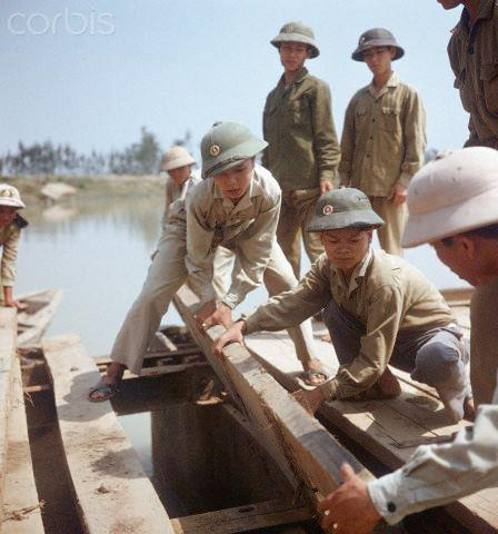 """01 Mar 1973, Dong Hoi, Vietnam --- Young Vietnamese people of a so-called youth brigade build a temporary bridge across a stretch of water near Dong Hoi in North Vietnam, shortly before the border to South Vietnam at the 17th degree of latitude, photographed in March 1973. The United States of America flew about 2,000 air attacks on cities and targets in North Vietnam during the """"Christmas bombings"""" in 1972. The peace agreement was signed on the 27th of January in 1973 in Paris. Photo: Werner Schulze --- Image by © Werner Schulze/dpa/Corbis © Corbis. All Rights Reserved."""