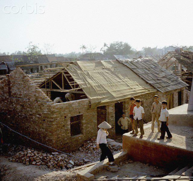 """01 Mar 1973, Hanoi, Vietnam --- Vietnamese children in front of a newly built house, photographed in March 1973 in war-destroyed Kham Thien, a part of Hanoi in North Vietnam. The United States of America flew about 2,000 air attacks on cities and targets in North Vietnam during the """"Christmas bombings"""" in 1972. The peace agreement was signed on the 27th of January in 1973 in Paris. Photo: Werner Schulze --- Image by © Werner Schulze/dpa/Corbis © Corbis. All Rights Reserved."""