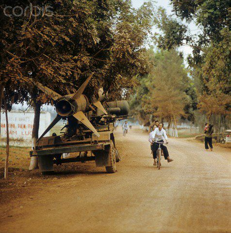 01 Mar 1973, Hanoi, Vietnam --- Vietnamese people drive on bicycles past a parked missile at the side of the street in North Vietnam along Street Number 1, photographed in March 1973. Street Number 1, built by the French, as main connection line to South Vietnam with more than 1,500 kilometres lenght was a strategic target in Vietnam War, The United States of America flew about 2,000 air attacks on cities and targets in North Vietnam during the