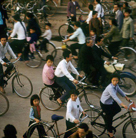 01 Mar 1973, Hanoi, Vietnam --- Vietnamese people with bicycles and a motorcycle from the GDR in a street in Hanoi in North Vietnam, photographed in March 1973. The United States of America flew about 2,000 air attacks on cities and targets in North Vietnam during the
