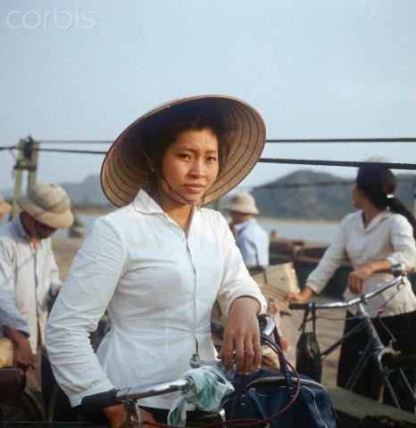 "01 Mar 1973, Dong Hoi, Vietnam --- A Vietnamese woman with a bicycle and a straw hat on a ferry, photographed in March 1973 in North Vietnam, south-eastern of Dong Hoi near the 17th degree of latitude, which is regarded as the border to South Vietnam. The United States of America flew about 2,000 air attacks on cities and targets in North Vietnam during the ""Christmas bombings"" in 1972. The peace agreement was signed on the 27th of January in 1973 in Paris. Photo: Werner Schulze --- Image by © Werner Schulze/dpa/Corbis © Corbis. All Rights Reserved."