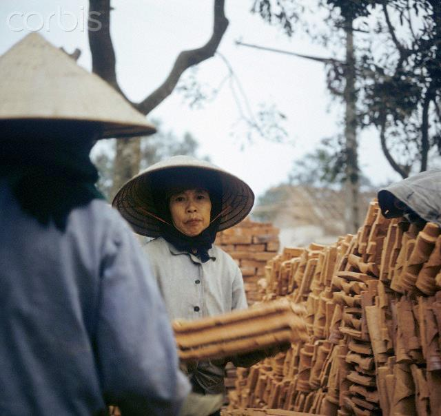 "01 Mar 1973, Hanoi, Vietnam --- Two women load stones from a roofing tile factory on a lorry near Hanoi, photographed in Mach 1973 in The United States of America flew about 2,000 air attacks on cities and targets in North Vietnam during the ""Christmas bombings"" in 1972. The peace agreement was signed on the 27th of January in 1973 in Paris. Inhabitants dig out reusable bricks out of ruins. Photo: Werner Schulze --- Image by © Werner Schulze/dpa/Corbis © Corbis. All Rights Reserved."