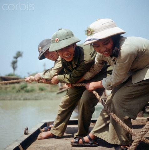 "01 Mar 1973, Dong Hoi, Vietnam --- Young Vietnamese people of a so-called youth brigade build a temporary bridge across a stretch of water near Dong Hoi in North Vietnam, shortly before the border to South Vietnam at the 17th degree of latitude, photographed in March 1973. The United States of America flew about 2,000 air attacks on cities and targets in North Vietnam during the ""Christmas bombings"" in 1972. The peace agreement was signed on the 27th of January in 1973 in Paris. Photo: Werner Schulze --- Image by © Werner Schulze/dpa/Corbis © Corbis. All Rights Reserved."