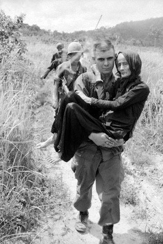 BE045475  03 Aug 1965, Vietnam --- Original caption: 8/3/1965-Ba Ria, South Vietnam: An aged woman injured by a U.S.-Vietnamese air strike on a Buddist monastery 40 miles southeast of Saigon is carried to a hospital by airborne private Carl Champ of Furgitsville, West Virginia.  American and Vietnamese were carrying out joint operations against the Viet Cong in the area when the monastery was bombed. --- Image by © Bettmann/CORBIS © Corbis.  All Rights Reserved.